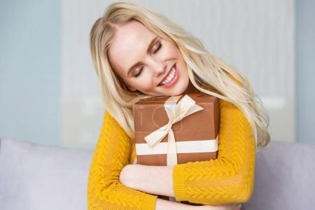 beautiful happy blonde girl with closed eyes hugging gift box at home