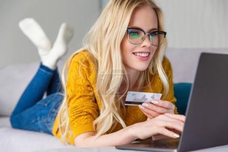 Photo pour Belle fille blonde souriante dans les lunettes tenant la carte de crédit et en utilisant un ordinateur portable à la maison - image libre de droit