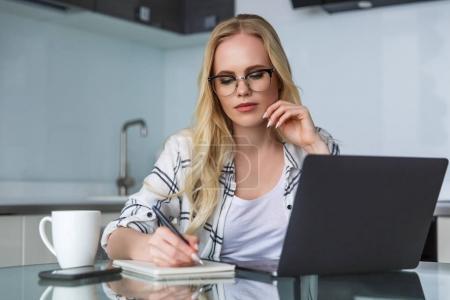 Photo pour Jeune femme à lunettes à l'aide d'ordinateur portable et prendre des notes tout en travaillant à la maison - image libre de droit