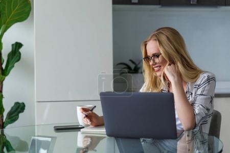 Photo pour Souriante jeune femme à lunettes à l'aide d'ordinateur portable et de prendre des notes tout en travaillant à la maison - image libre de droit