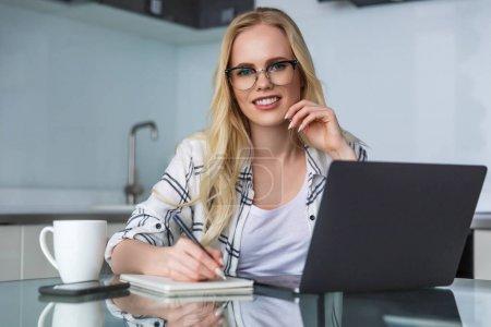 Photo pour Belle jeune femme à lunettes, souriant à la caméra lors de l'utilisation d'ordinateur portable et prendre des notes à la maison - image libre de droit