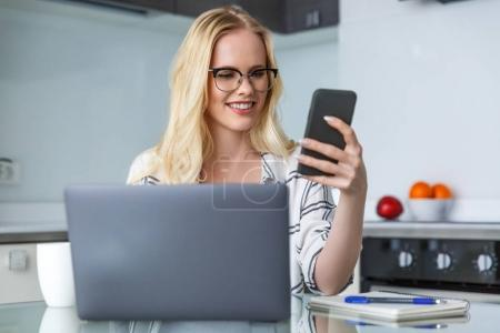 Photo pour Belle jeune femme souriante en lunettes de vue avec le smartphone et l'ordinateur portable à la maison - image libre de droit