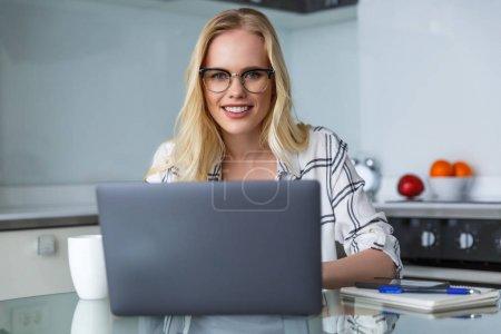Photo pour Belle jeune femme à lunettes, souriant à la caméra tout en travaillant avec l'ordinateur portable à la maison - image libre de droit