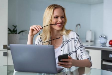 Photo pour Souriante jeune femme tenant lunettes et en regardant loin alors qu'il travaillait avec des appareils numériques à la maison - image libre de droit