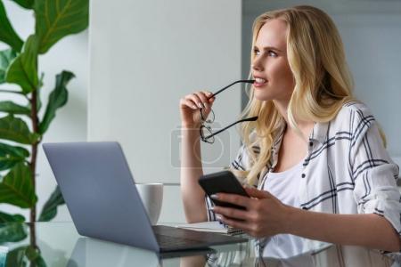 Photo pour Jeune femme tenant lunettes et en regardant loin alors qu'il travaillait avec des appareils numériques à la maison - image libre de droit