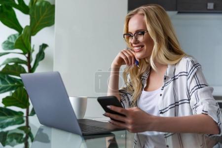 Photo pour Belle femme souriante à l'aide d'ordinateur portable et le smartphone tout en travaillant à la maison bureau - image libre de droit