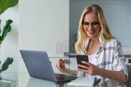 Photo for Smiling young woman holding smartphone and using laptop while working at home - Royalty Free Image