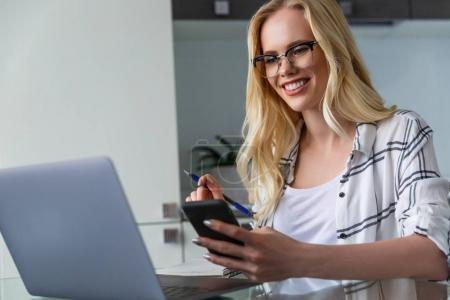 smiling young woman in eyeglasses holding smartphone and using laptop while working at home