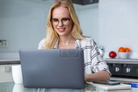 Photo pour Femme blonde souriante à lunettes à l'aide de portable alors qu'il travaillait à la maison - image libre de droit