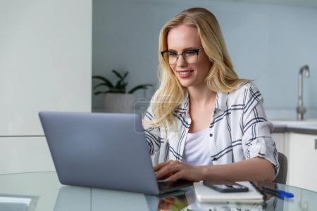 Photo for Beautiful smiling young woman in eyeglasses using laptop while working at home - Royalty Free Image