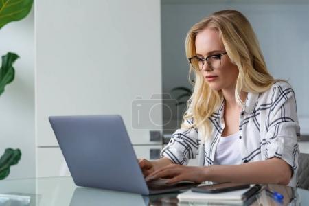 Photo pour Jeune femme blonde, à l'aide de portable alors qu'il travaillait à la maison - image libre de droit