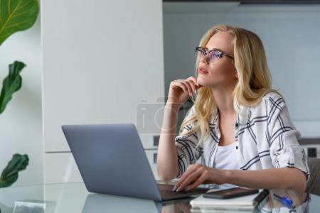 Photo pour Belle femme blonde songeuse à l'aide de portable alors qu'il travaillait à la maison - image libre de droit