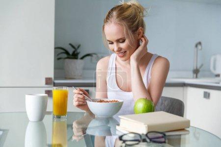 Photo pour Belle jeune femme souriante manger muesli pour le petit déjeuner à la maison - image libre de droit