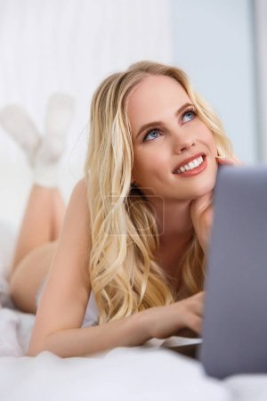 beautiful pensive blonde girl using laptop and looking up while lying on bed