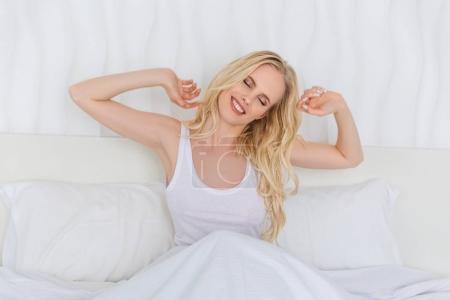 Photo pour Belle fille blonde souriante avec les yeux fermés étirant les mains tout en étant assis sur le lit le matin - image libre de droit