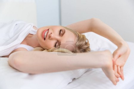 Photo for Beautiful smiling blonde girl stretching and waking up in bed - Royalty Free Image