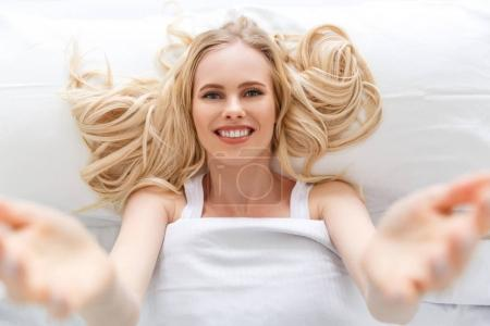 top view of beautiful young woman smiling at camera while lying in bed