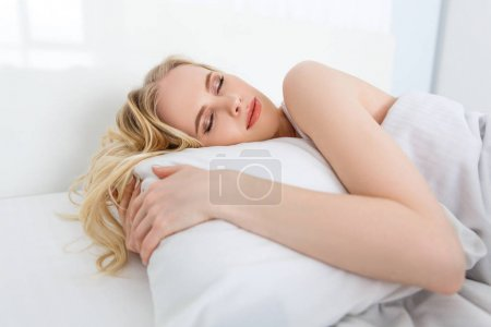 Photo for Beautiful young blonde woman sleeping on white pillow in bed - Royalty Free Image