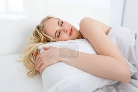 beautiful young blonde woman sleeping on white pillow in bed