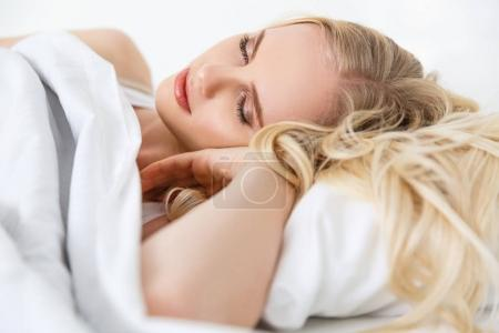 beautiful blonde girl sleeping in bed