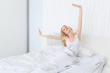 Photo for Beautiful happy young woman waking up while sitting on bed - Royalty Free Image