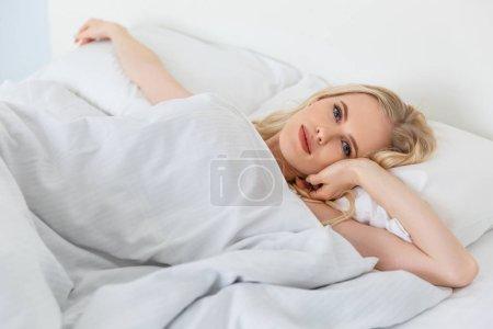 Photo pour Belle jeune femme blonde allongée dans le lit et regardant la caméra - image libre de droit