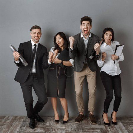 happy multicultural business people with folders and notebooks standing at grey wall