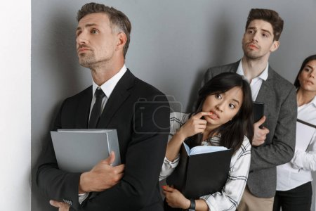 Photo for Multicultural business people with folders and notebooks standing in row while waiting for job interview - Royalty Free Image