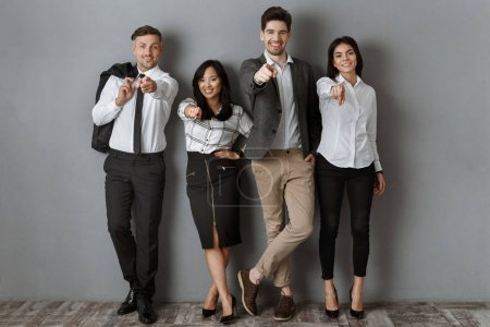 Photo for Multicultural business people in formal wear pointing at camera while standing at grey wall - Royalty Free Image