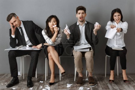 stressed multicultural business people with folders and notebooks waiting for job interview