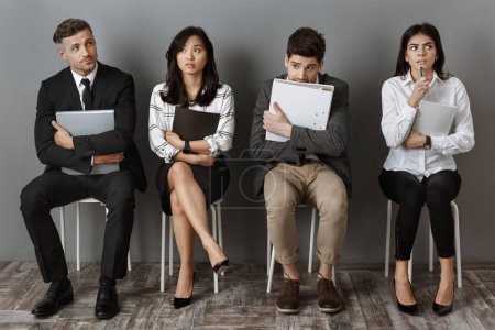 scared and pensive multicultural business people with folders and notebooks waiting for job interview