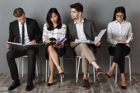 focused multicultural business people with folders and notebooks waiting for job interview
