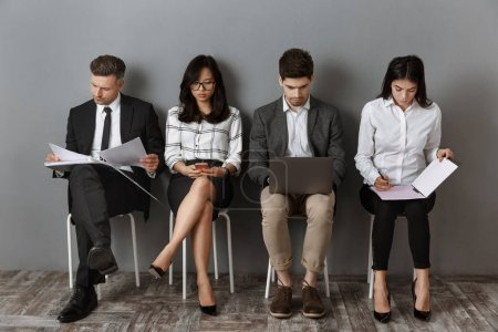 Photo for Focused multiethnic business people with digital devices and folders waiting for job interview - Royalty Free Image