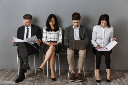 Foto de Personas de negocios multiétnicos enfocados con dispositivos digitales y carpetas a la espera de entrevista de trabajo - Imagen libre de derechos