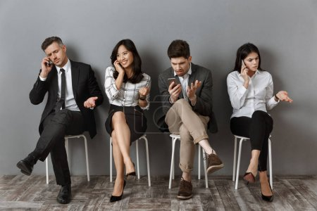 interracial business people in formal wear with smartphones waiting for job interview