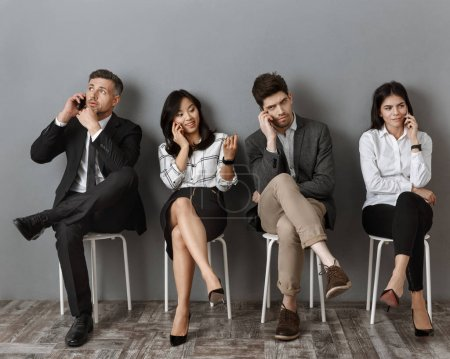 interracial business people talking on smartphones while waiting for job interview