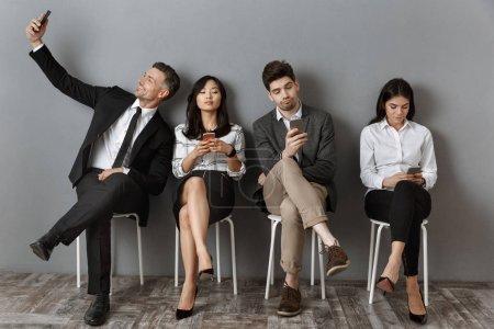 Photo pour Interview de gens d'affaires Interracial tenues avec les smartphones en attente de travail - image libre de droit