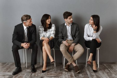 interracial business people in formal wear having conversation together while waiting for job interview