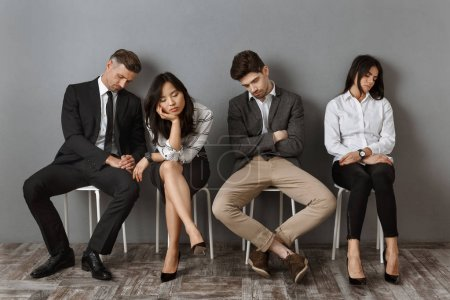 tired interracial business people in formal wear sleeping on chairs while waiting for job interview