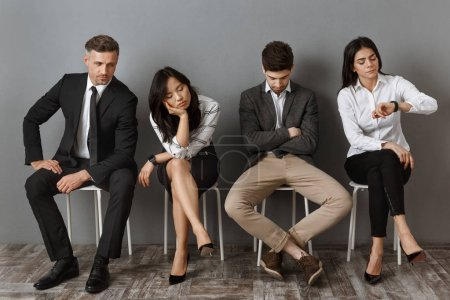 bored and tired interracial business people in formal wear waiting for job interview