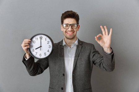 Portrait de sourire homme d'affaires avec horloge dans la main montrant signe OK sur fond de mur gris