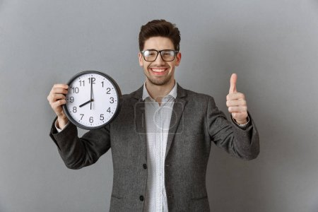 portrait of smiling businessman with clock in hand showing thumb up on grey wall background