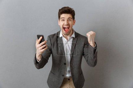 Photo pour Portrait d'homme d'affaires heureux avec smartphone gestuelle sur fond de mur gris - image libre de droit