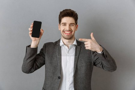 portrait of smiling businessman pointing at smartphone with blank screen in hand against grey wall background