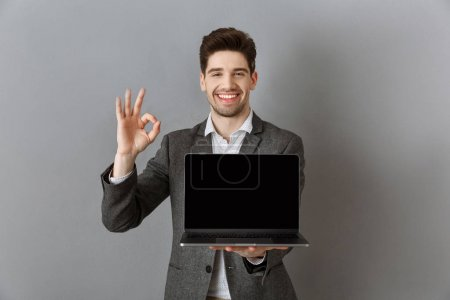 Photo for Portrait of smiling businessman in suit with laptop with blank screen showing ok sign against grey wall background - Royalty Free Image