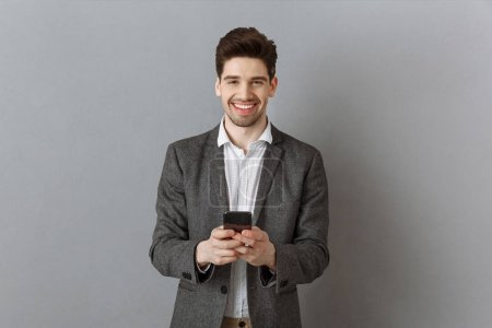 portrait of smiling businessman with smartphone against grey wall background