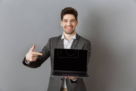 portrait of smiling businessman in suit pointing at laptop with blank screen against grey wall background