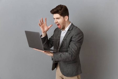 frustrated businessman in suit with laptop against grey wall background