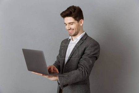 smiling businessman in suit using laptop against grey wall background