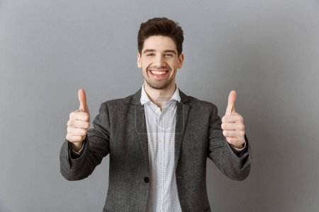 portrait of smiling businessman in suit showing thumbs up against grey wall